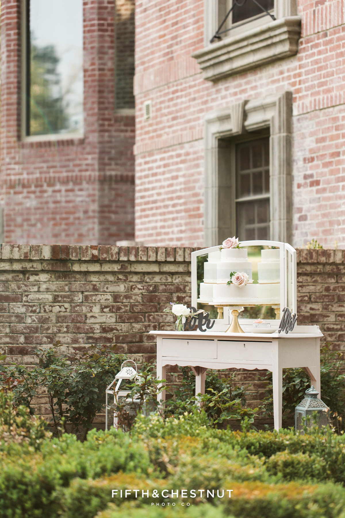 Dusty blue and white ombre watercolor wedding cake on a vintage white vanity table for a dusty blue private estate country french wedding inspiration styled shoot by Lake Tahoe Wedding photographer in front of a brick wall