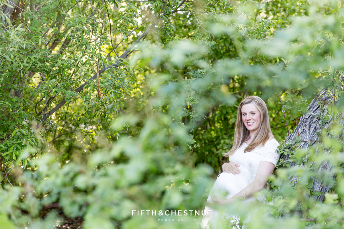maternity portrait of woman leaning against a tree photographed through leaves at Rancho San Rafael Park