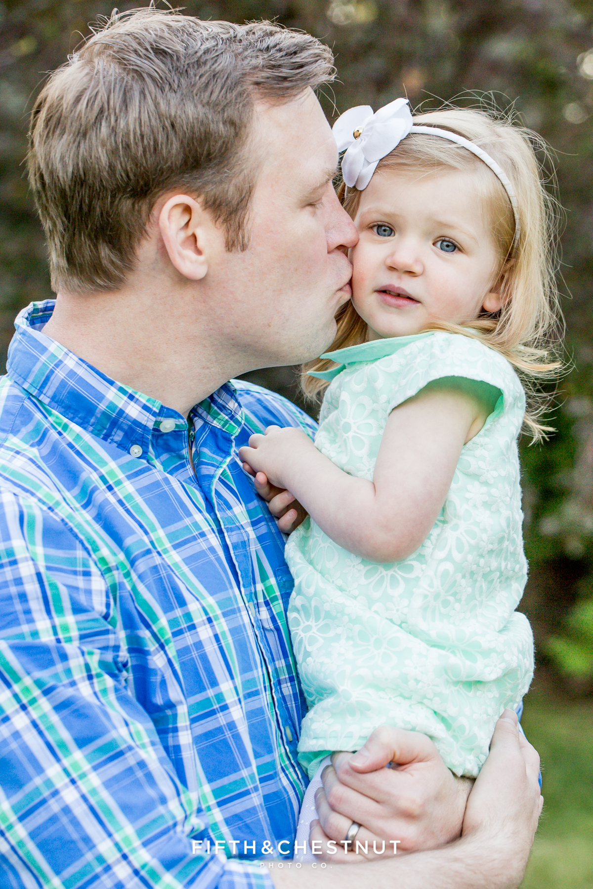 Dad gives two year old daughter a kiss on her cheek while being photographed at Rancho San Rafael by Reno Maternity Photographer