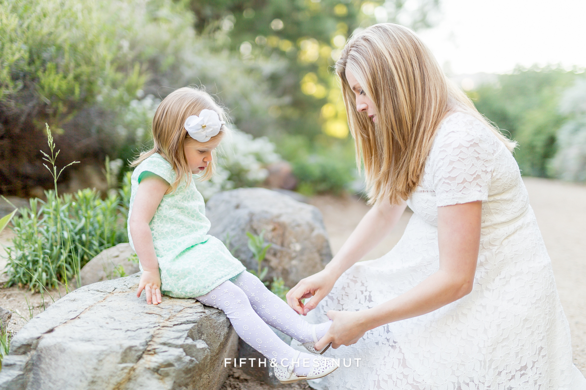 A pregnant mom fixes her toddler's shoes at a spring maternity photoshoot by Reno Maternity Photographer