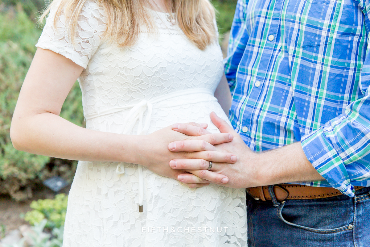 Husband and wife hold hands over pregnant belly for spring maternity portraits in Reno by Reno Maternity Photographer