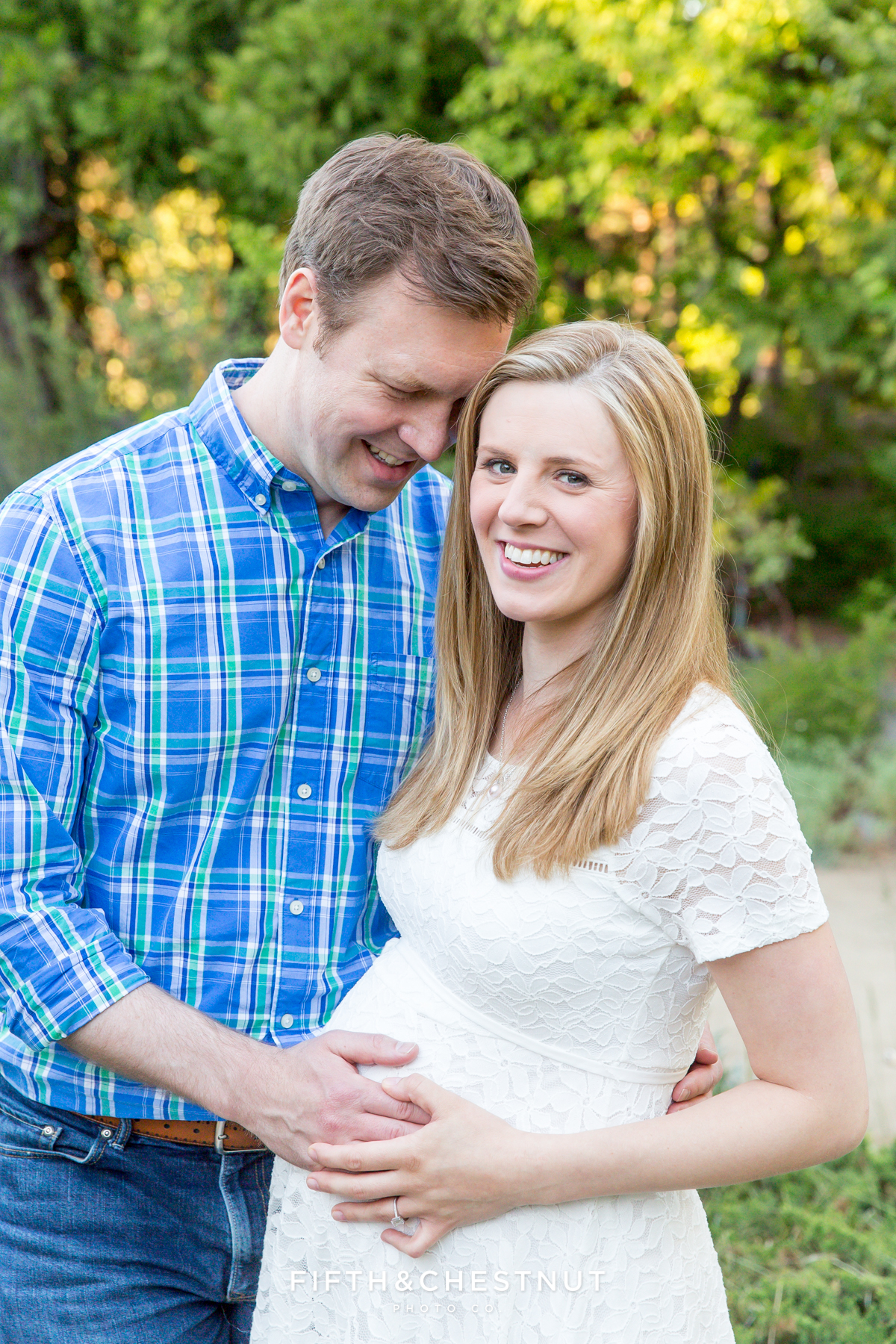 Pregnant woman poses for a picture with her husband for spring reno maternity portraits