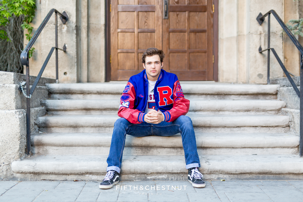 Portrait of Reno High School Senior wearing his letterman jacket on steps in Downtown Reno