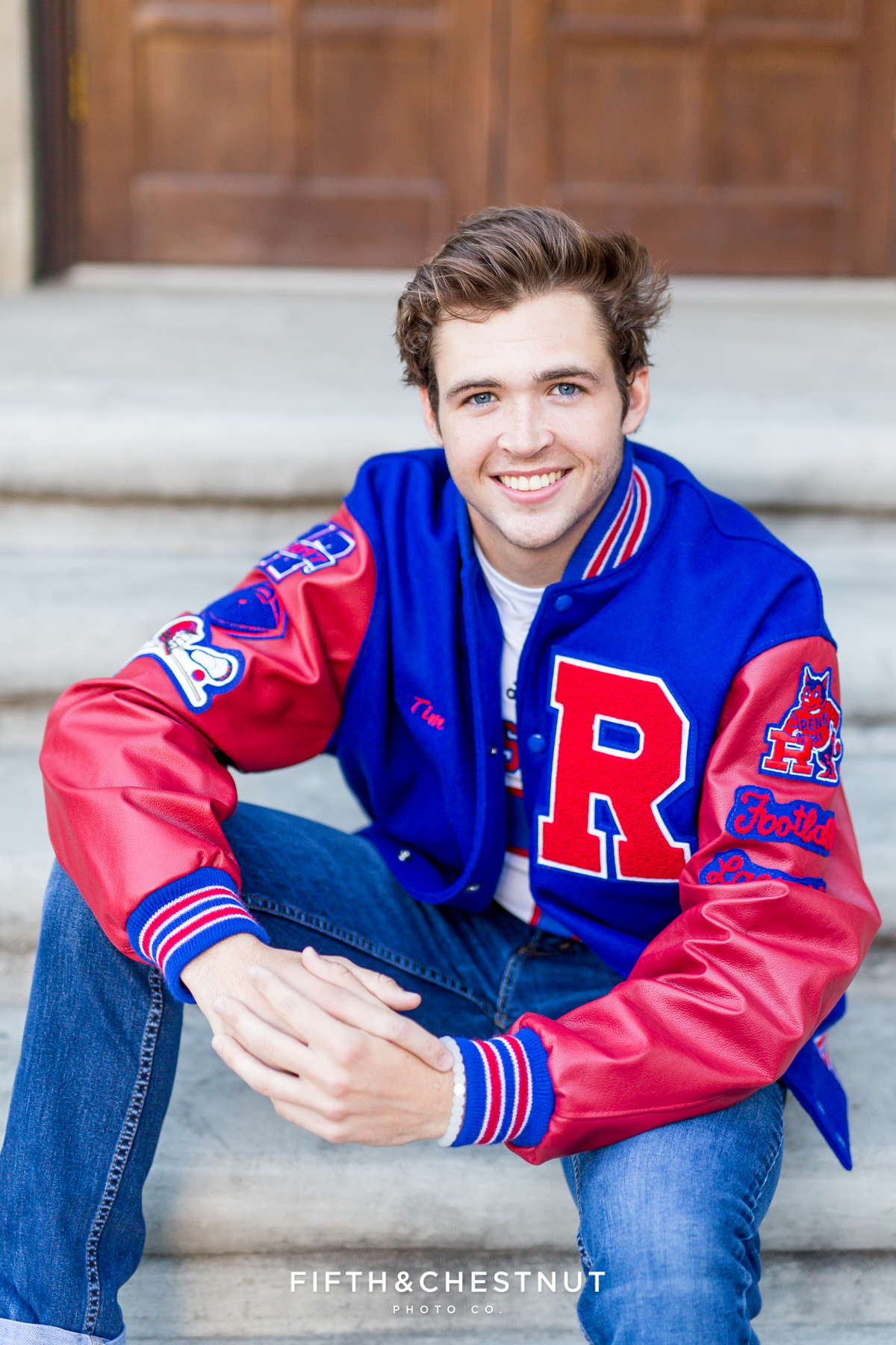Reno senior portraits of Reno High School Senior in Downtown Reno wearing his letterman jacket from Reno High School