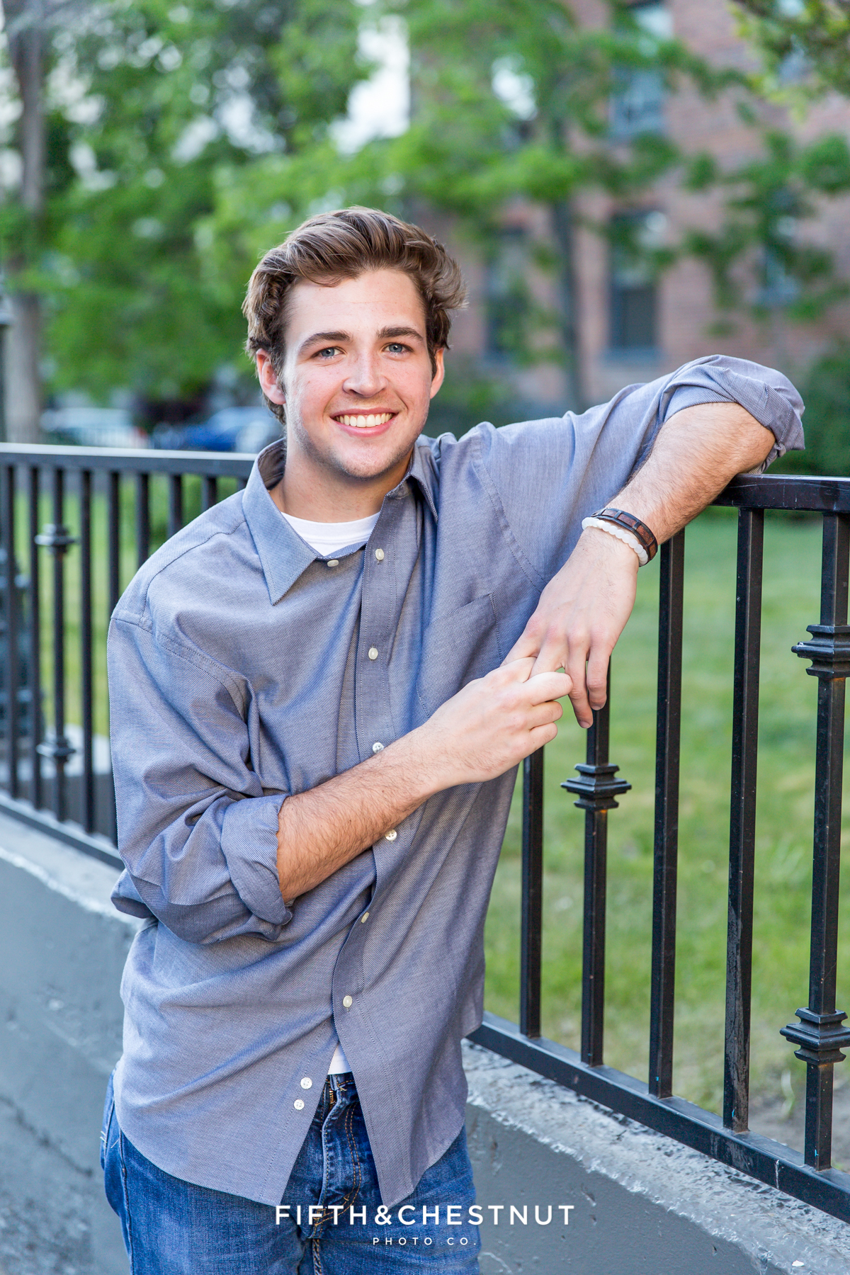 Reno senior portraits of Reno High School Senior Tim H wearing a blue shirt and leaning on an iron fence in the Downtown Reno area