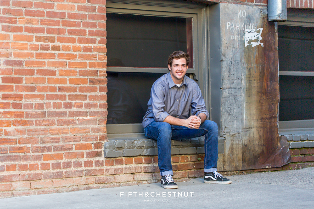 Reno senior portraits of Reno High School Senior Tim H wearing a blue shirt posing near Derby Supply Co in the Downtown Reno area
