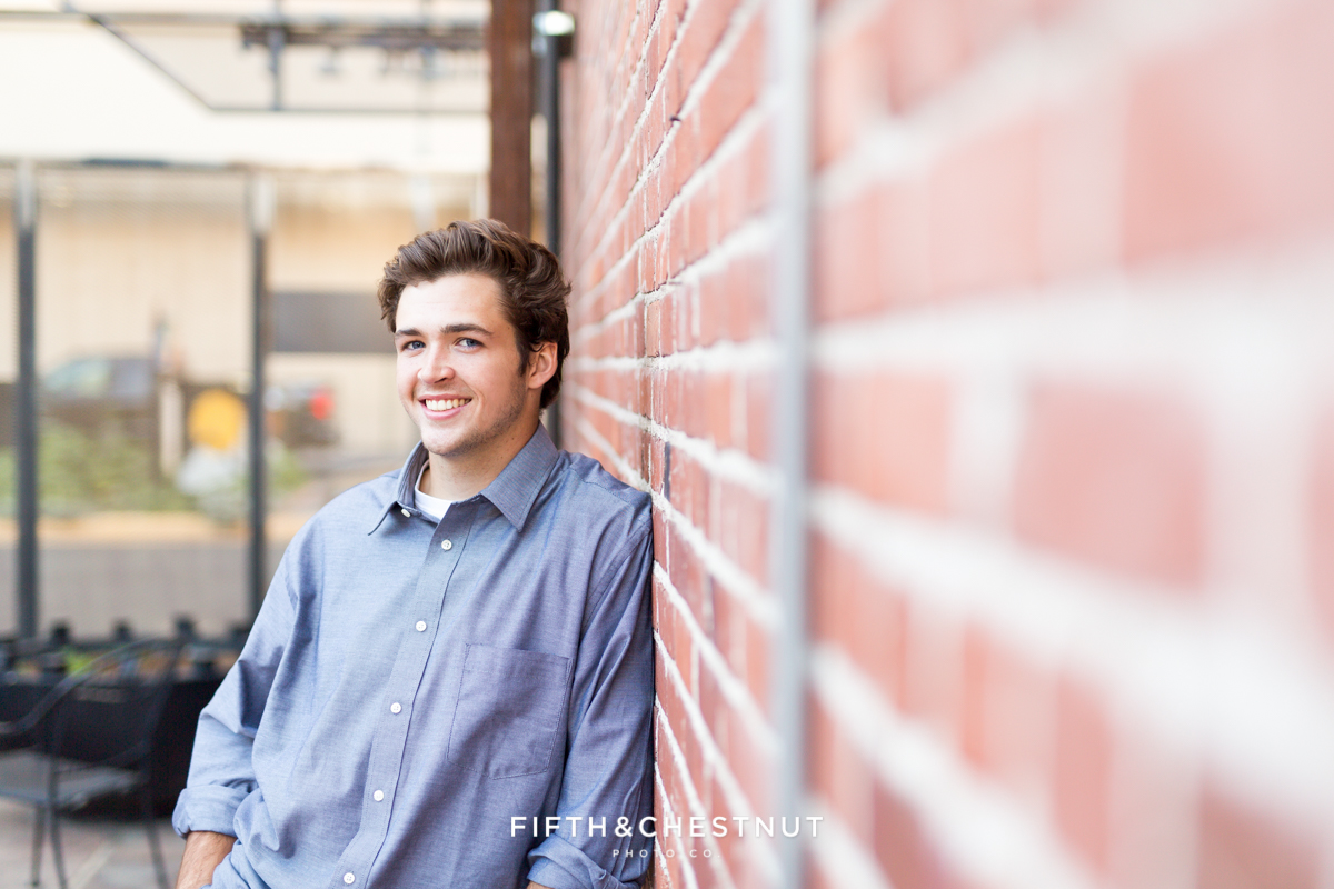 Reno High School Senior leaning against brick wall at West Street Market for his Reno Senior Portraits by Reno Senior Photographer