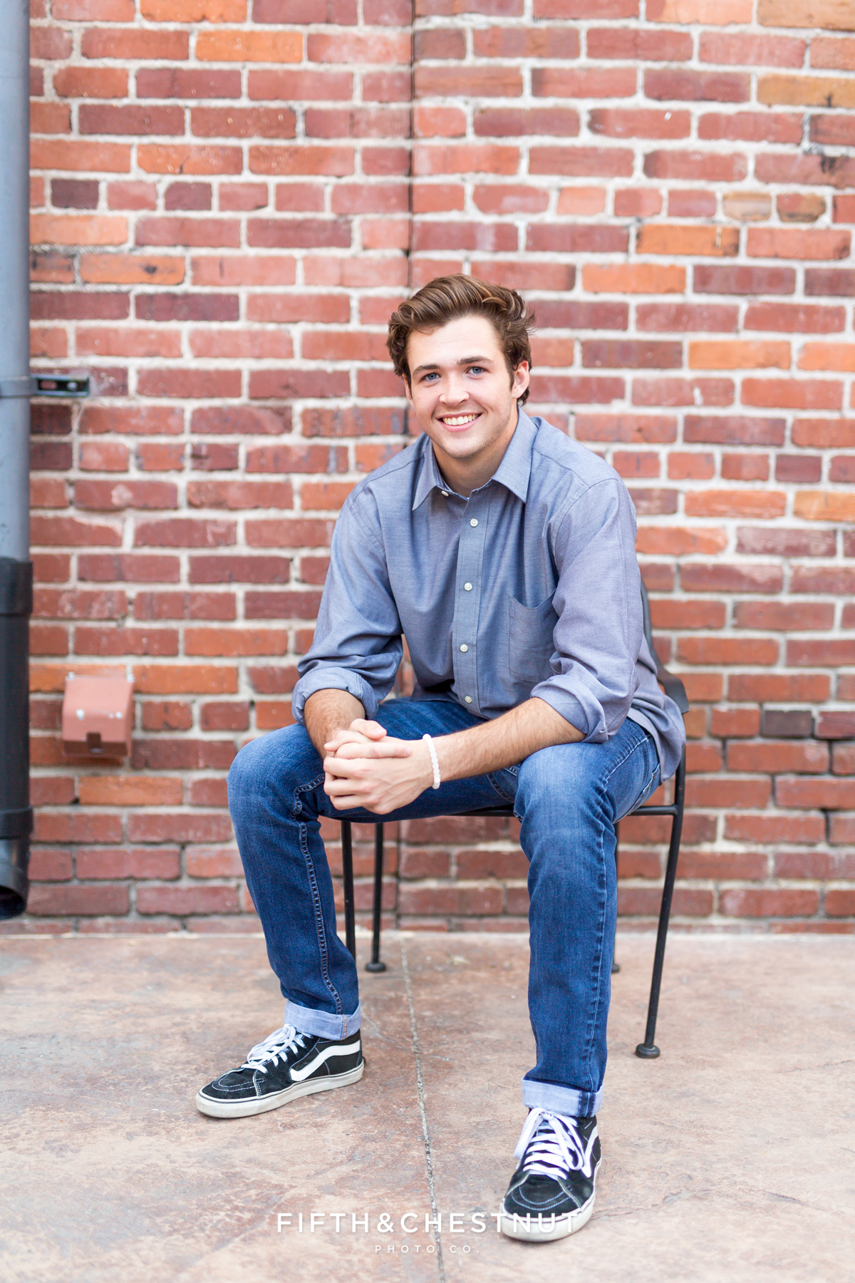 Reno High School Senior sitting in a chair in front of brick wall at West Street Market for his Reno Senior Portraits by Reno Senior Photographer