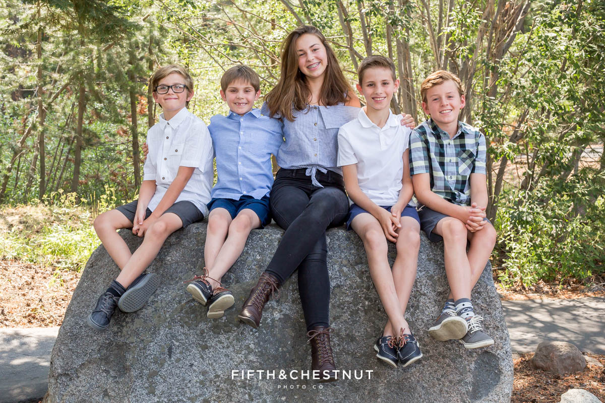 Portrait of grandchildren sitting together on a rock in Truckee