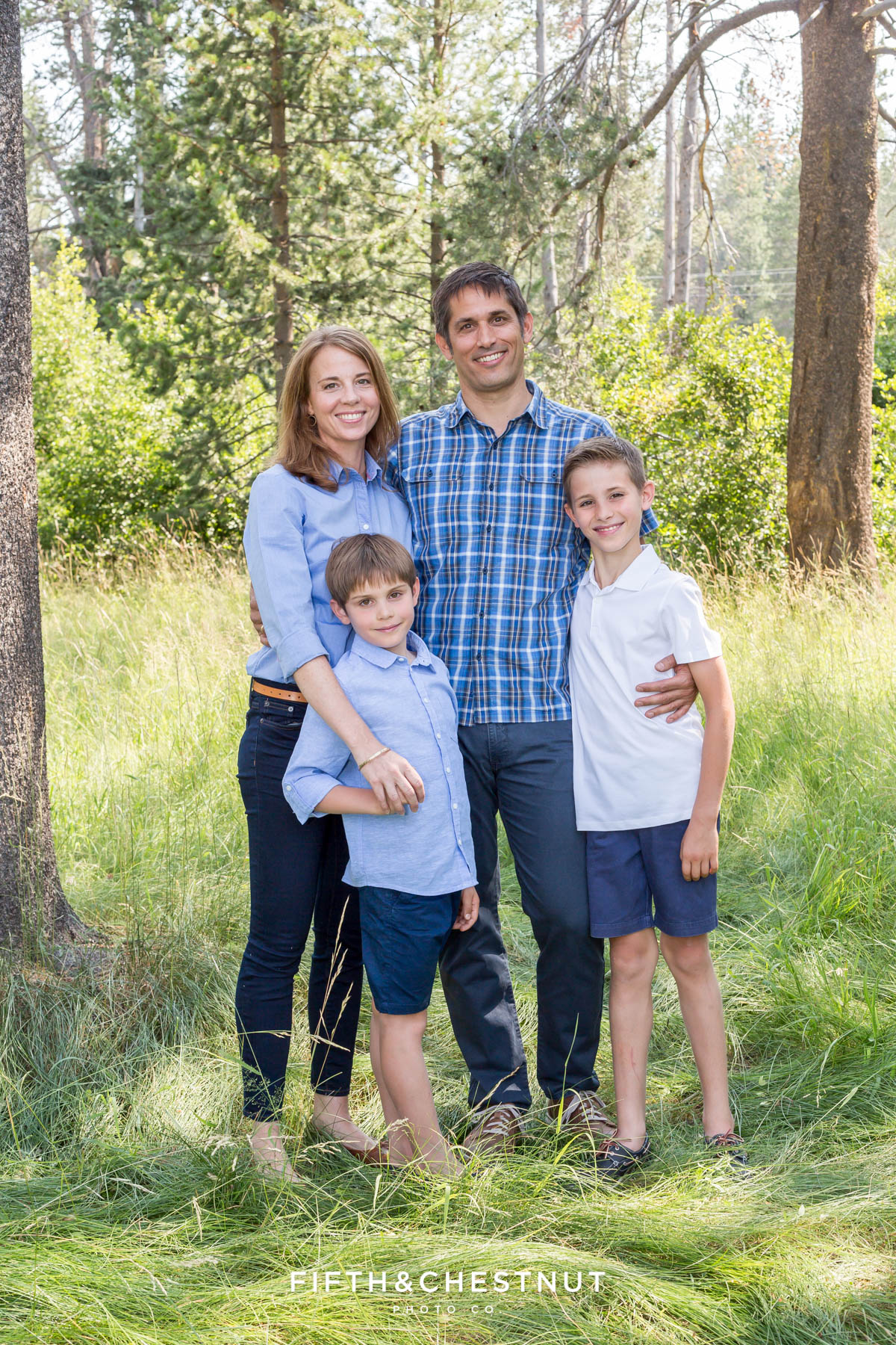 Mom, Dad and two sons stand proudly for a truckee family portrait