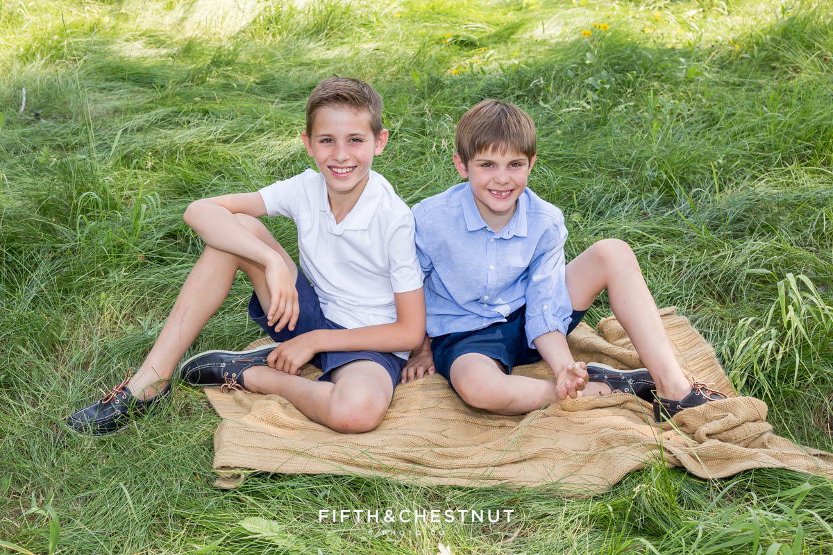 two boys sitting on a blanket laughing together