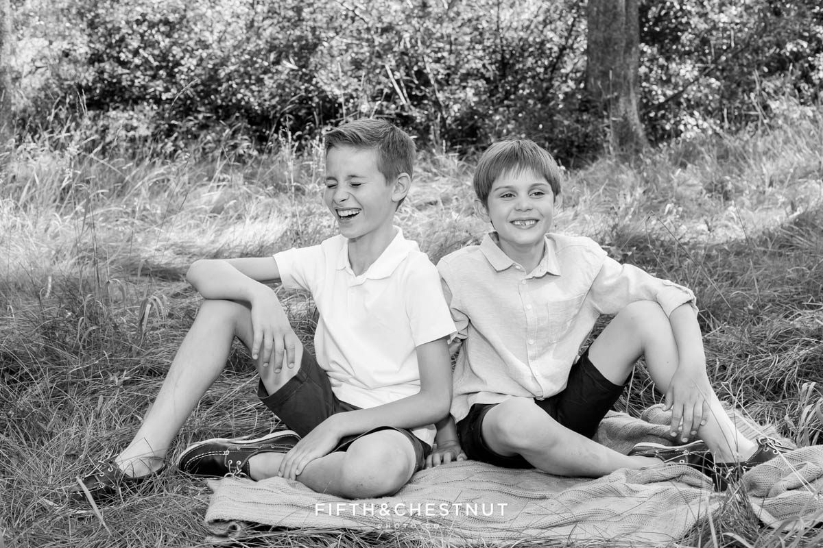 black and white photo of two brothers laughing on a blanket in Truckee, CA