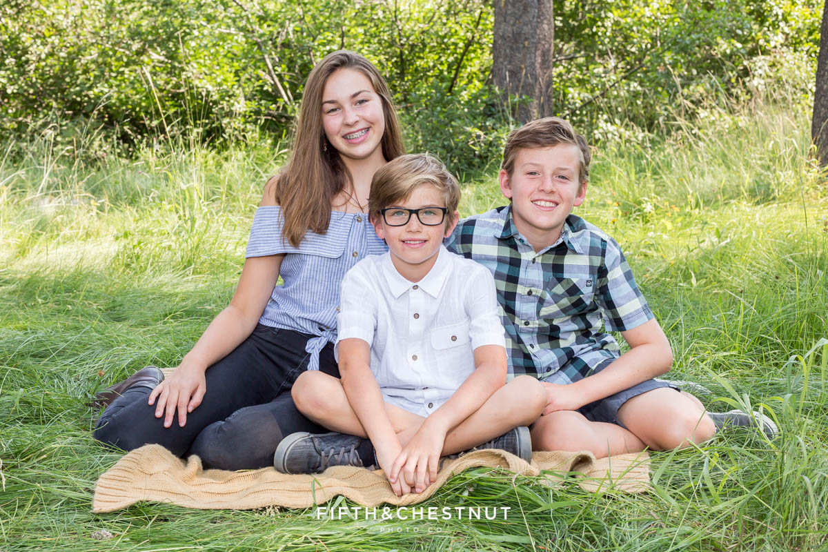 brothers and sister smile together for a truckee family portrait