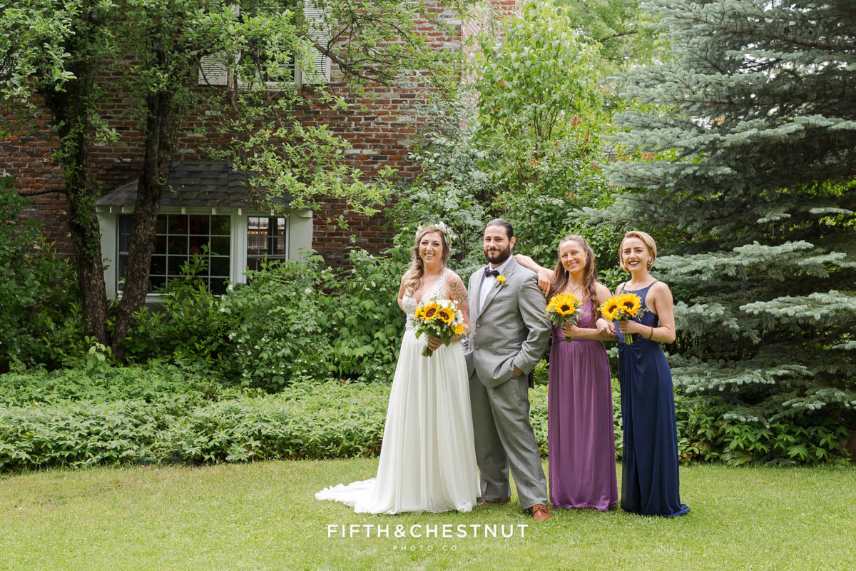 Bride, man of honor and bridesmaids dressed in royal blue and purple smile in front of the Twenty Mile House farm house for a photo by Graeagle Wedding Photographer
