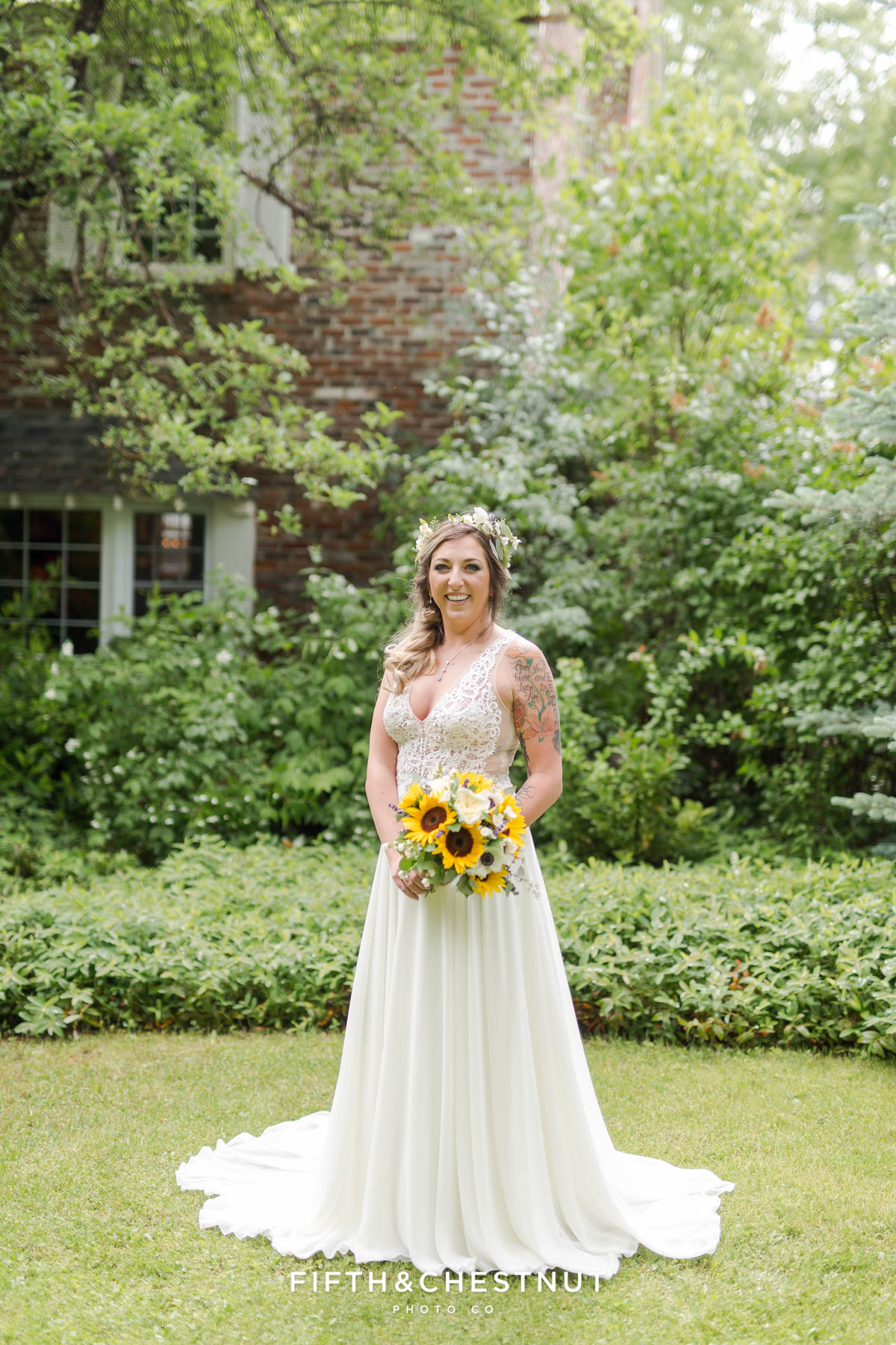 Bride stands in grass in front of farm house at the Twenty Mile house while holding a sunflower bouquet