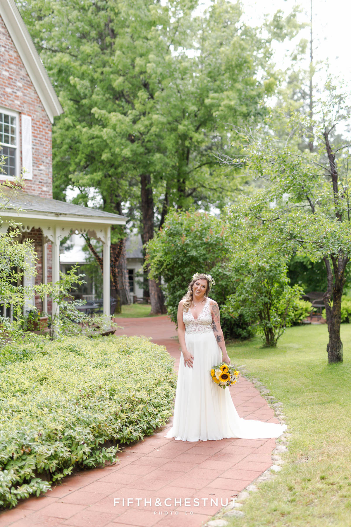 Bride laughs along brick path near the farm house at the Twenty Mile House before her boho chic wedding ceremony