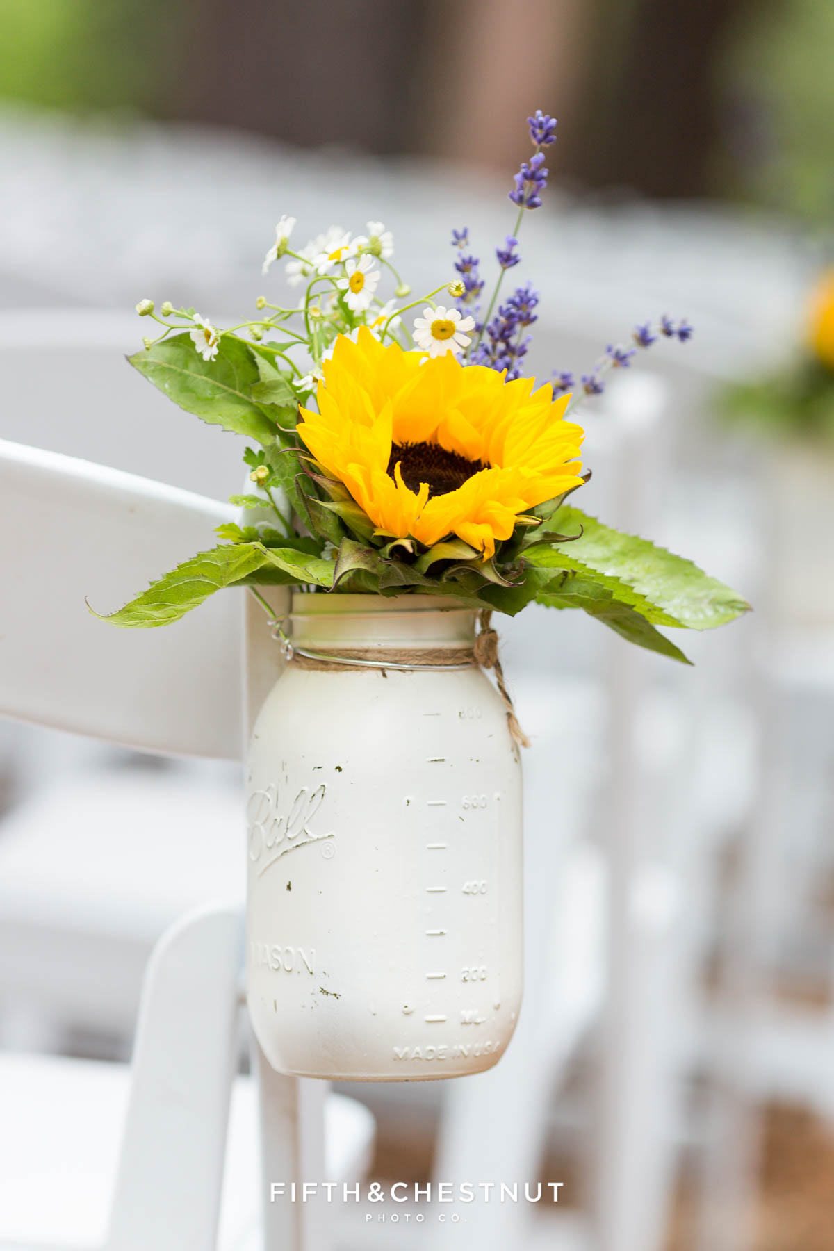 Sunflowers and other wild flowers in a white-painted mason jar with twine as wedding ceremony decor at the Twenty Mile House in Graeagle