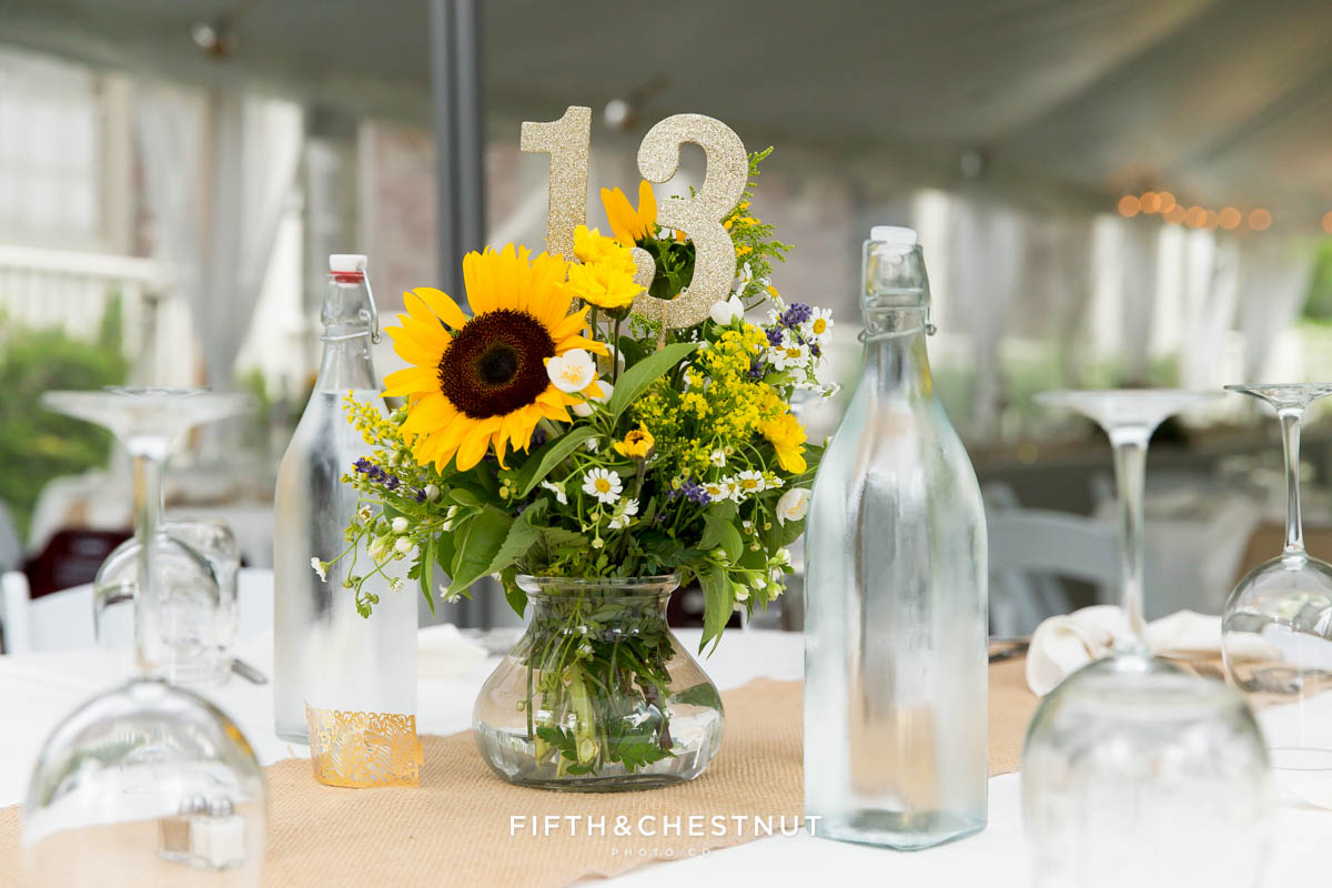sunflower wedding arrangement, table number and vintage water bottles on a reception table for a Twenty Mile House wedding