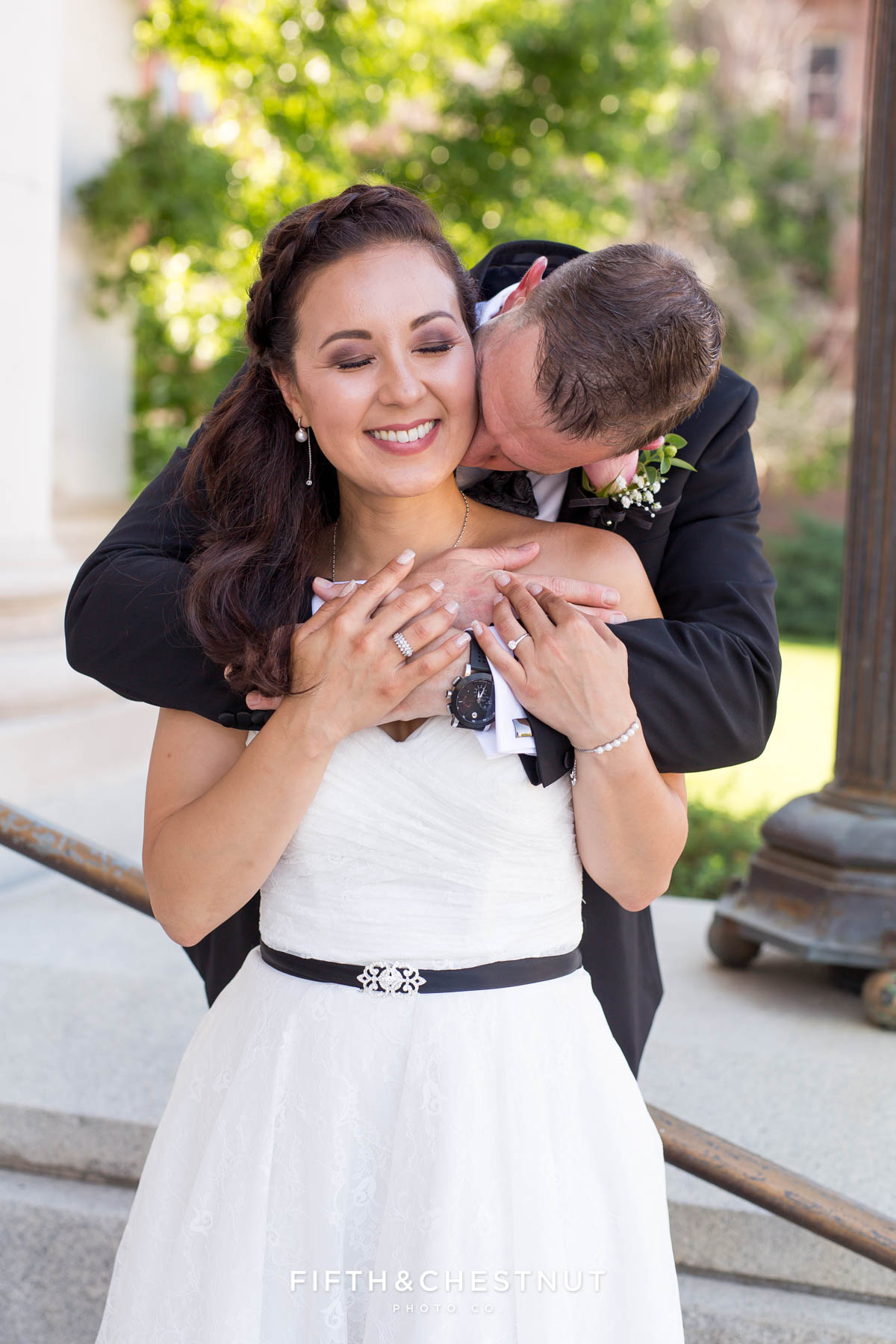 Groom kissing Bride's neck and making her smile