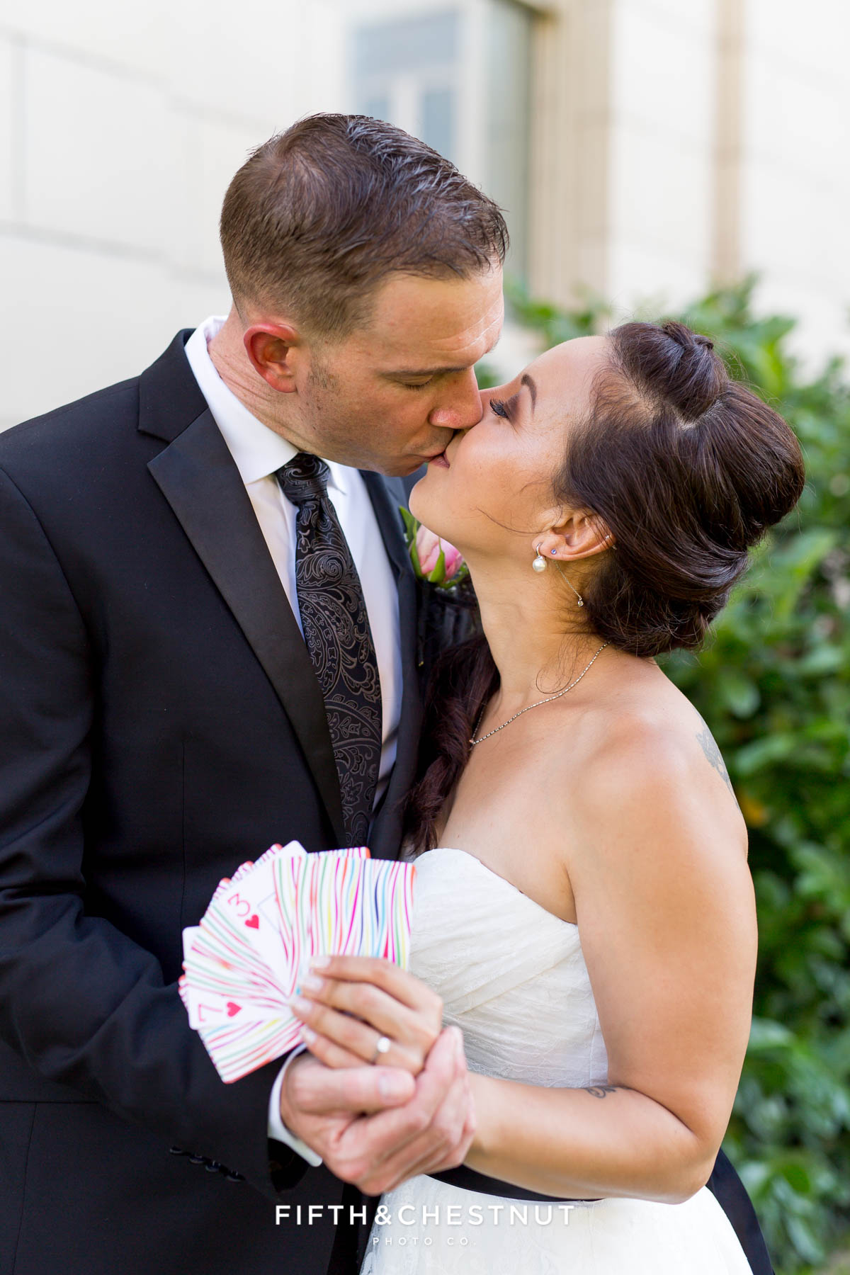 Bride and groom hold playing cards that display their wedding date in Reno while kissing