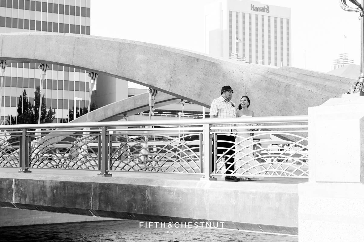 black and white image of a father leading his daughter down the virginia street bridge for a Downtown Reno Elopement at the river location of Antique Angel Wedding Chapel