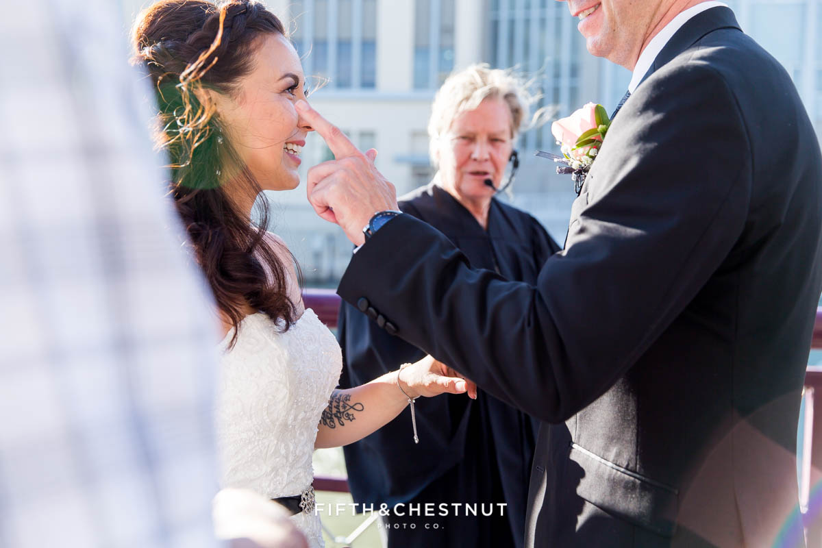 Groom wipes a tear from his bride's eyes