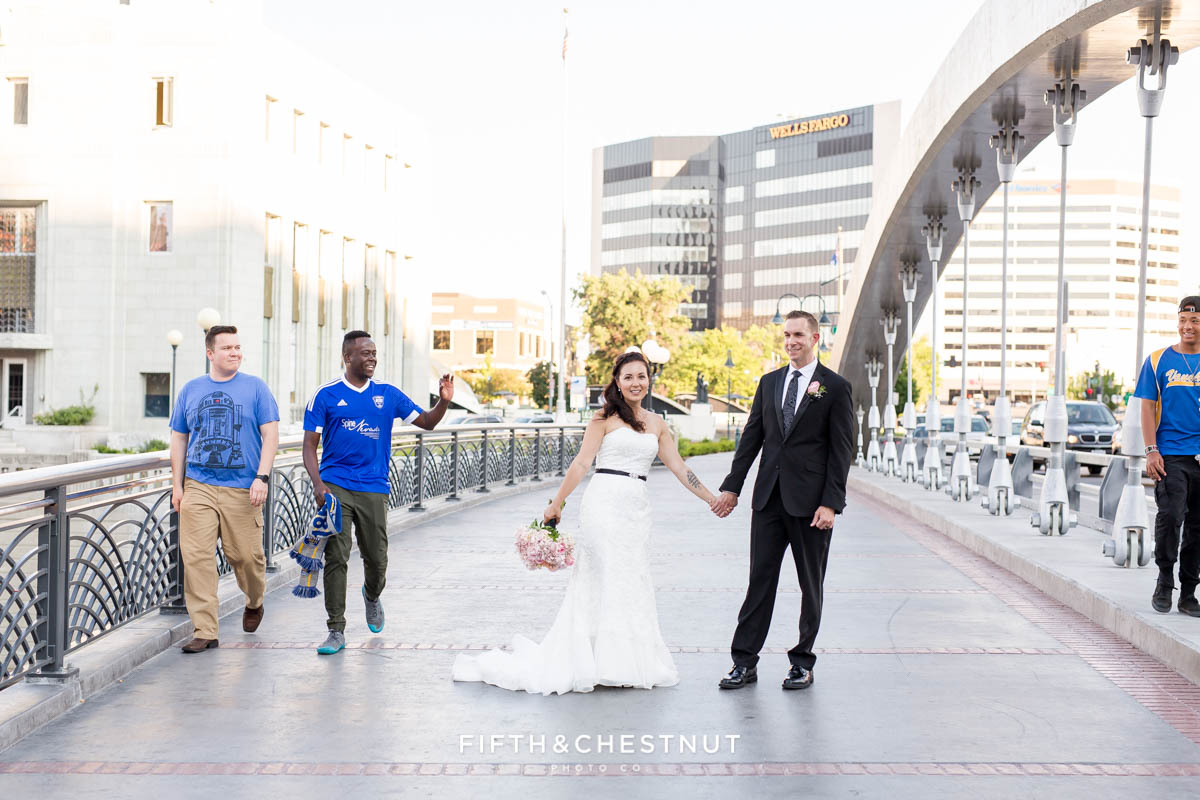 onlookers congratulate bride and groom on the virginia street bridge in reno