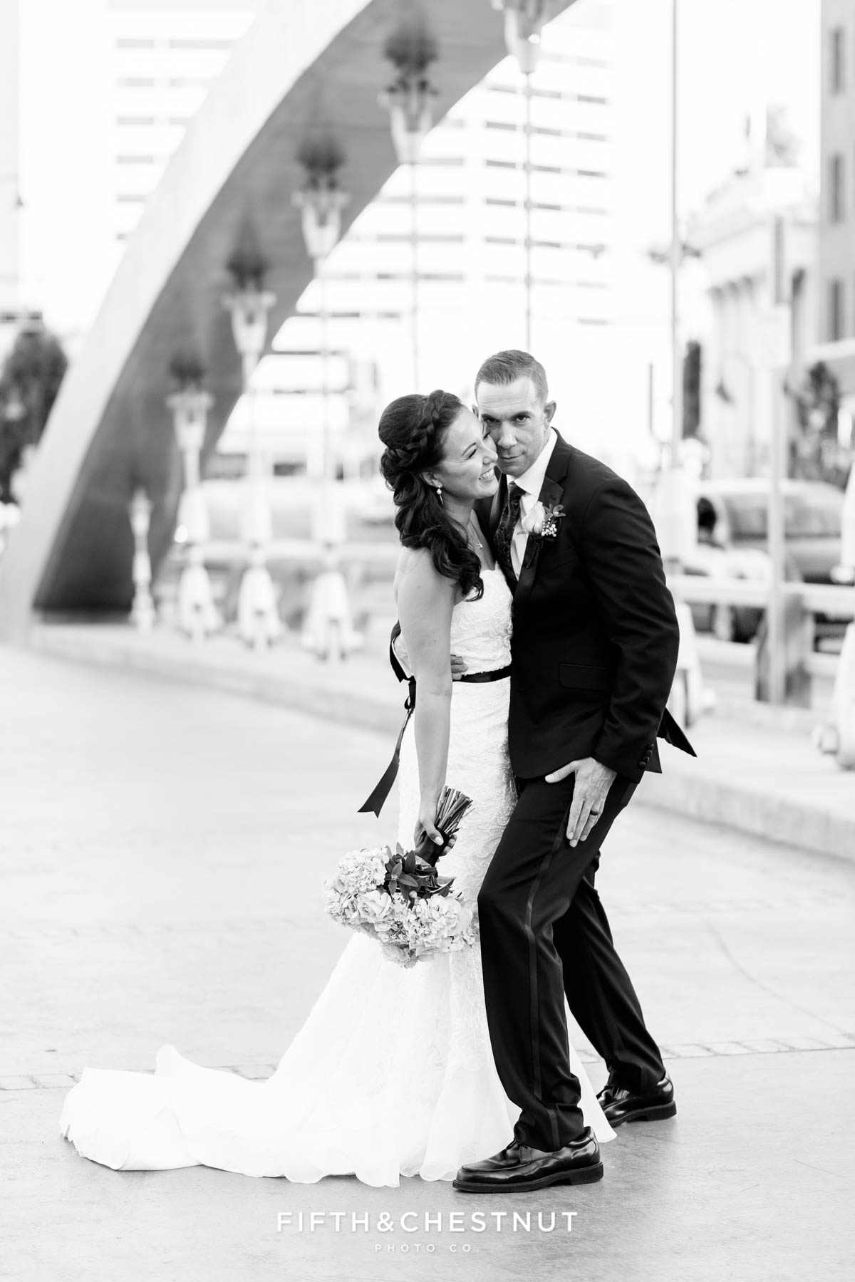bride and groom being silly together after their Downtown Reno Elopement on the virginia street bridge
