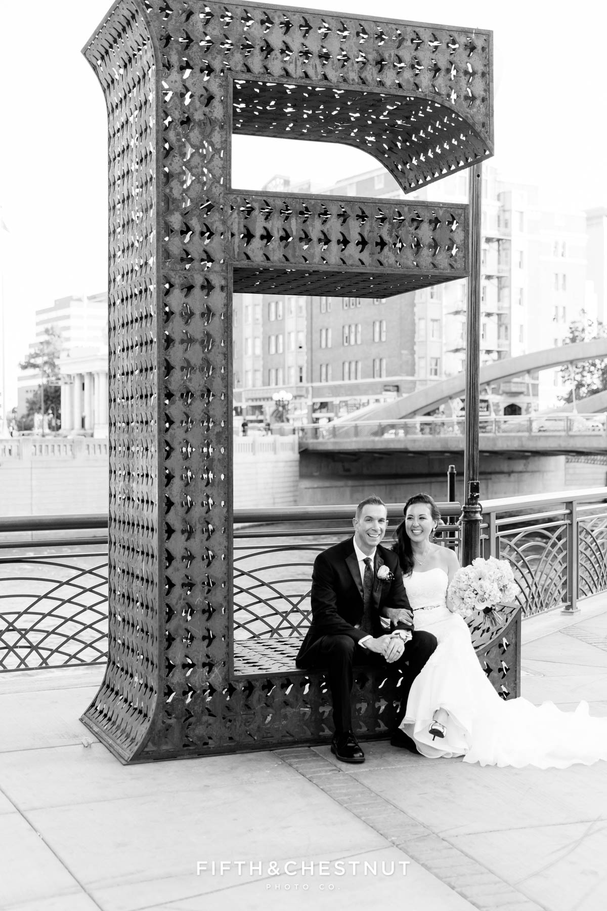 black and white photos of bride and groom sitting on the giant E of the believe installation in downtown reno
