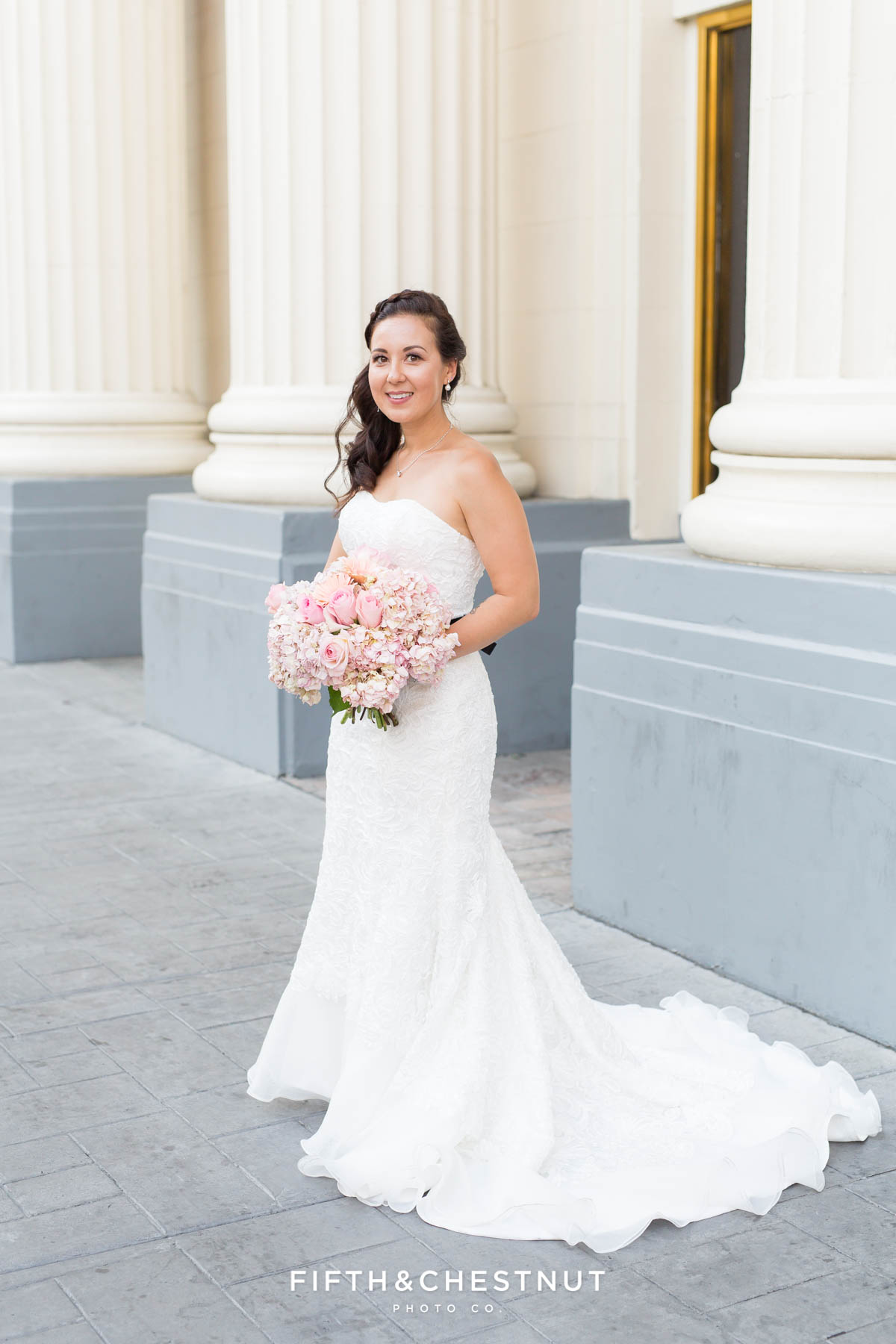 beautiful portrait of the bride at Harrah's in her long wedding gown while holding her pink wedding bouquet