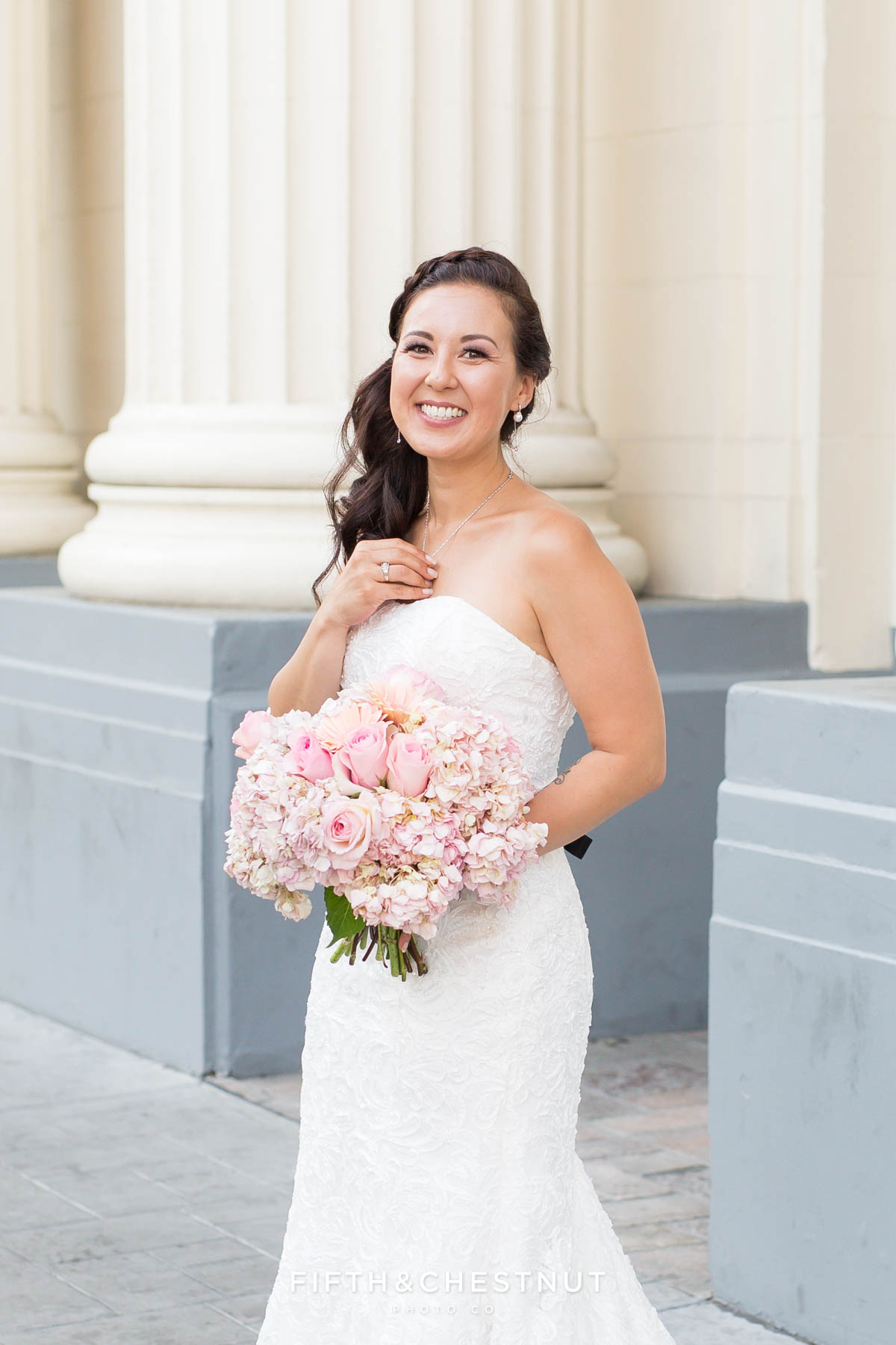Bride holds her necklace while posing for her Downtown Reno Elopement bridal portrait in front of Harrah's