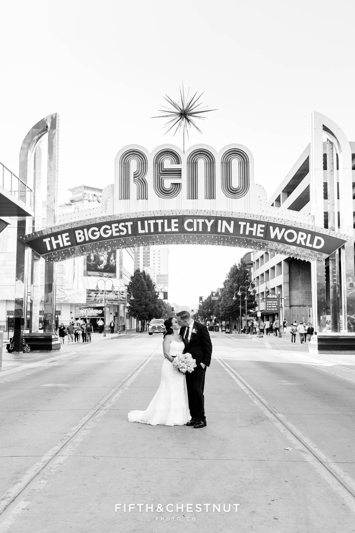 Black and white image of bride and groom kissing during thier Downtown Reno Elopement under the Reno Arch
