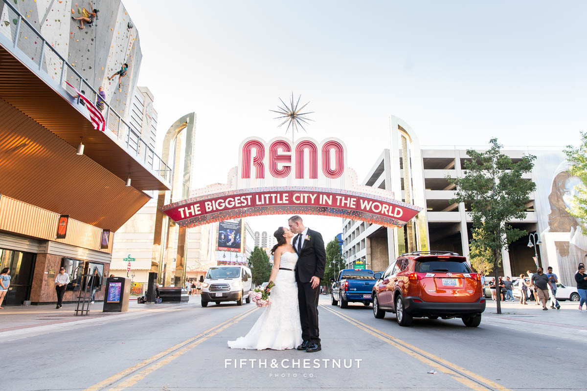 Bride and groom standing under the Reno Arch
