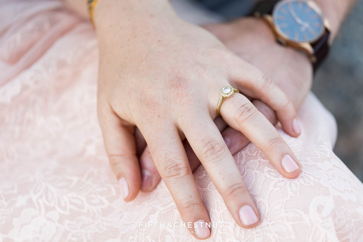 detail shot of bride-to-be's engagement ring while holding her hand above her partner's