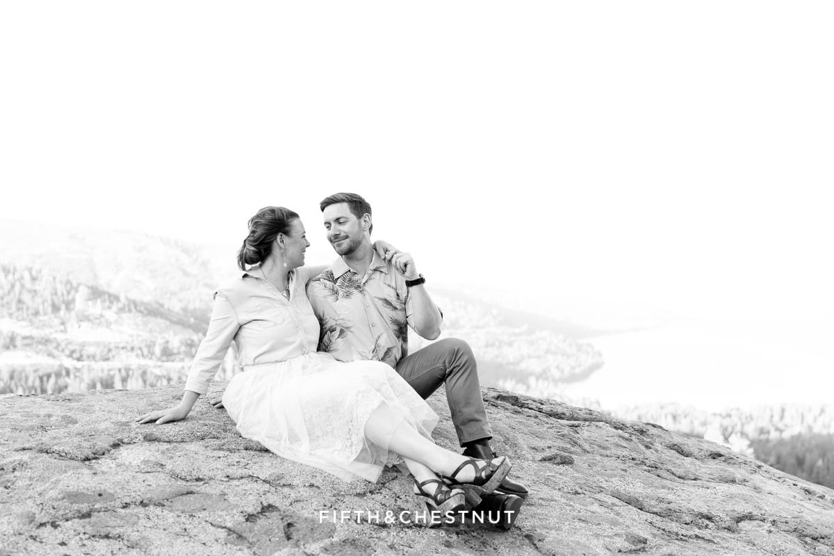 black and white photo of bride and groom sitting on rocks above Donner Lake