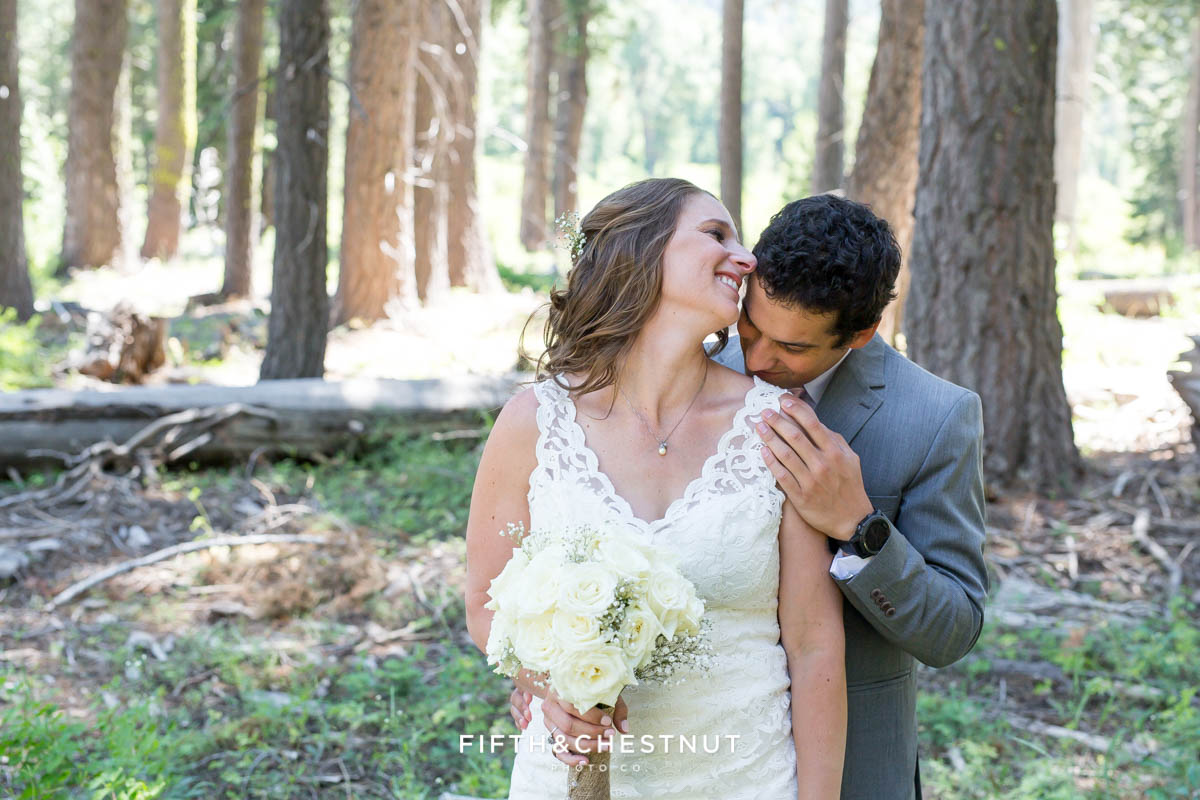 Groom kisses bride lightly on her shoulder after their sweet West shore wedding first look