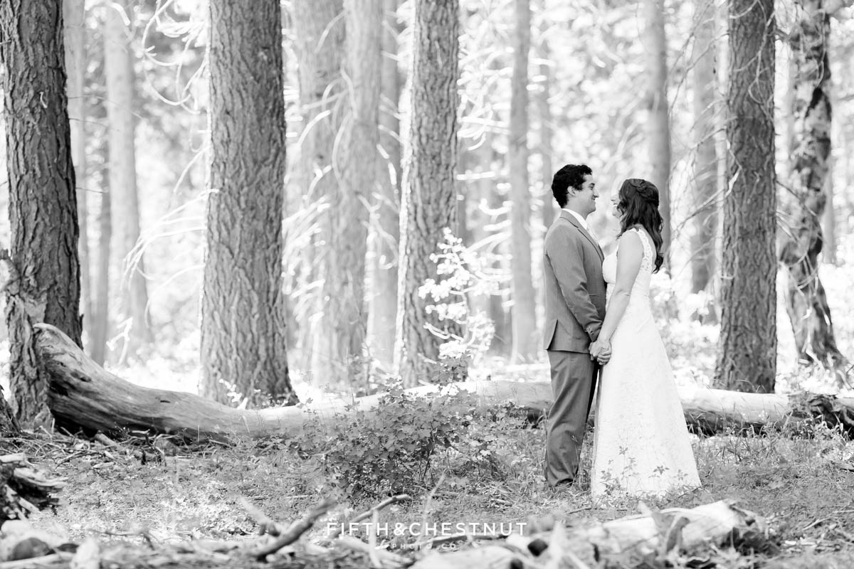black and white portrait of bride and groom holding hands in the forest after their West shore wedding first look