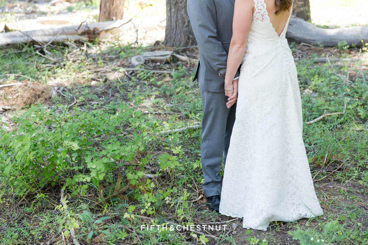 Bride and groom hold hands in the forest after their West shore wedding first look