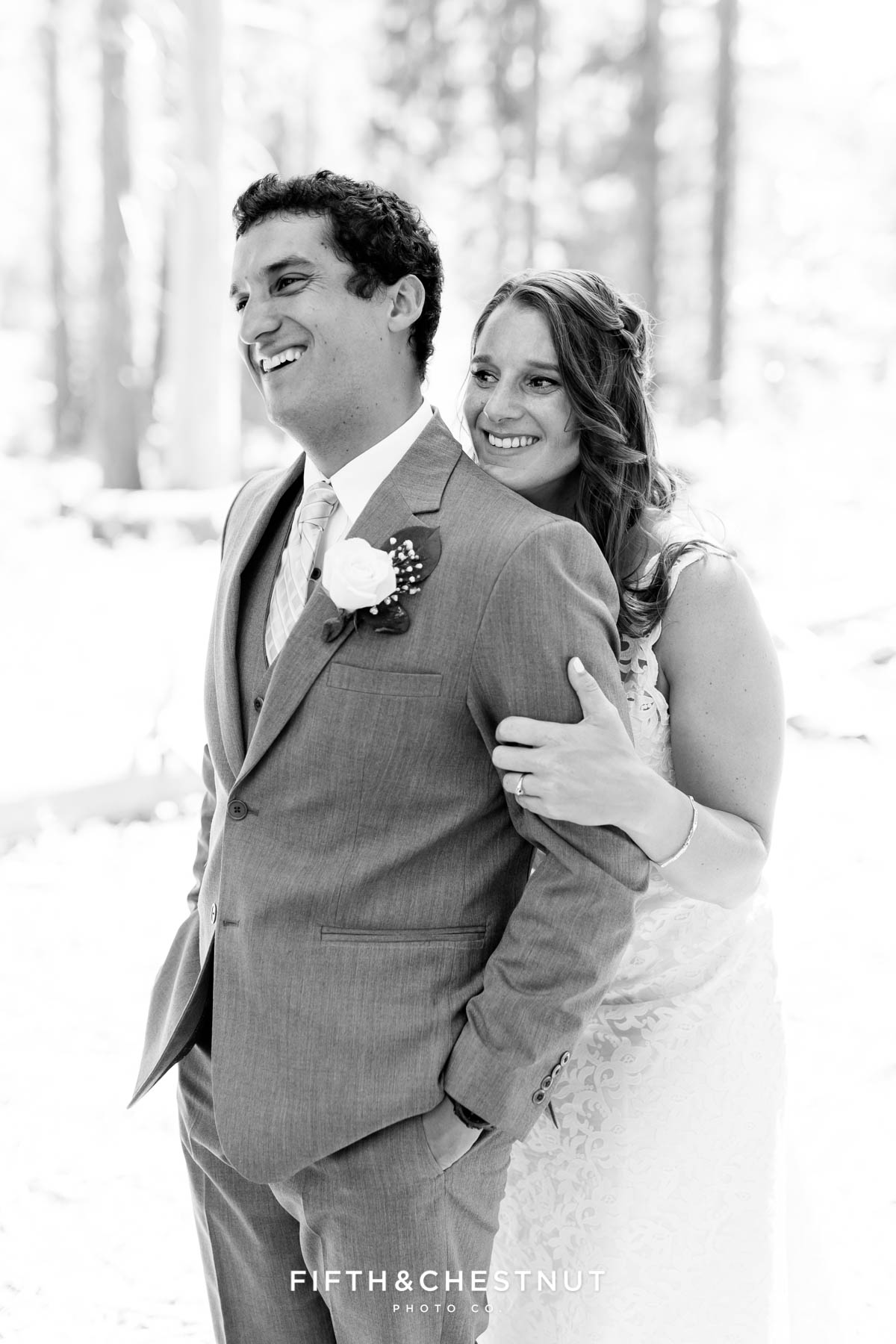 Bride embraces groom from behind after their sweet West shore wedding first look