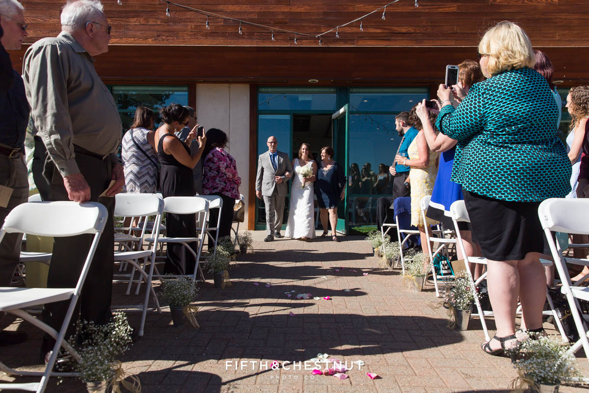 Bride walks down the aisle for her North Lake Tahoe Wedding ceremony in the bright sun with her mom and dad by her side