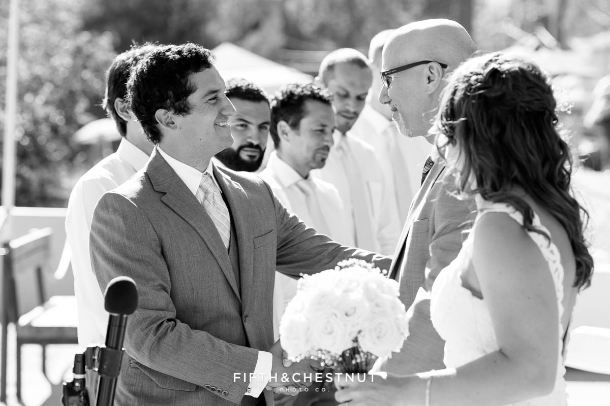 groom shakes hands with father of the bride after he walks his daughter down the aisle