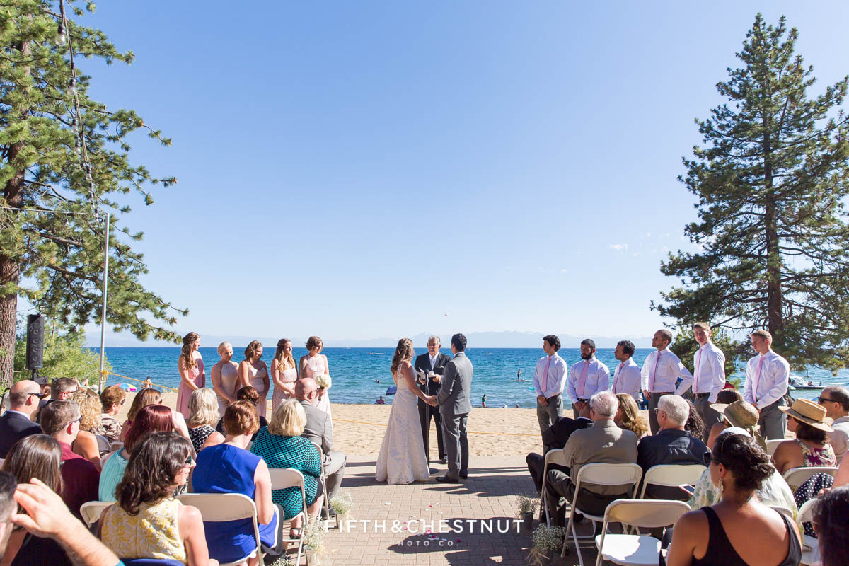 wide shot of lake tahoe wedding ceremony on the beach on a clear beautiful day
