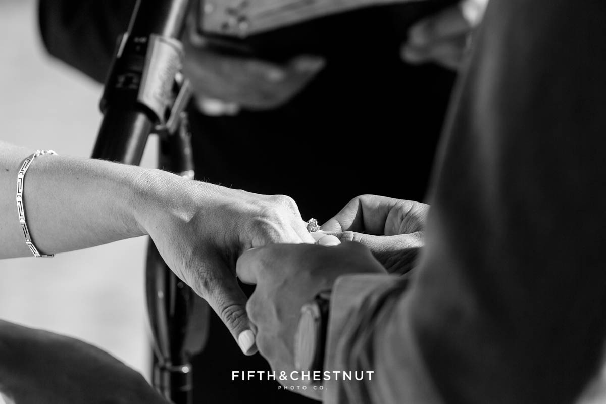 Black and white photo of the groom placing his wife's wedding ring on her ring finger