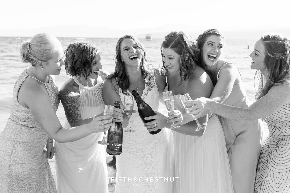 Bride and bridesmaids pop a bottle of champagne and laugh and smile for a Tahoe wedding on the beach of North Lake Tahoe