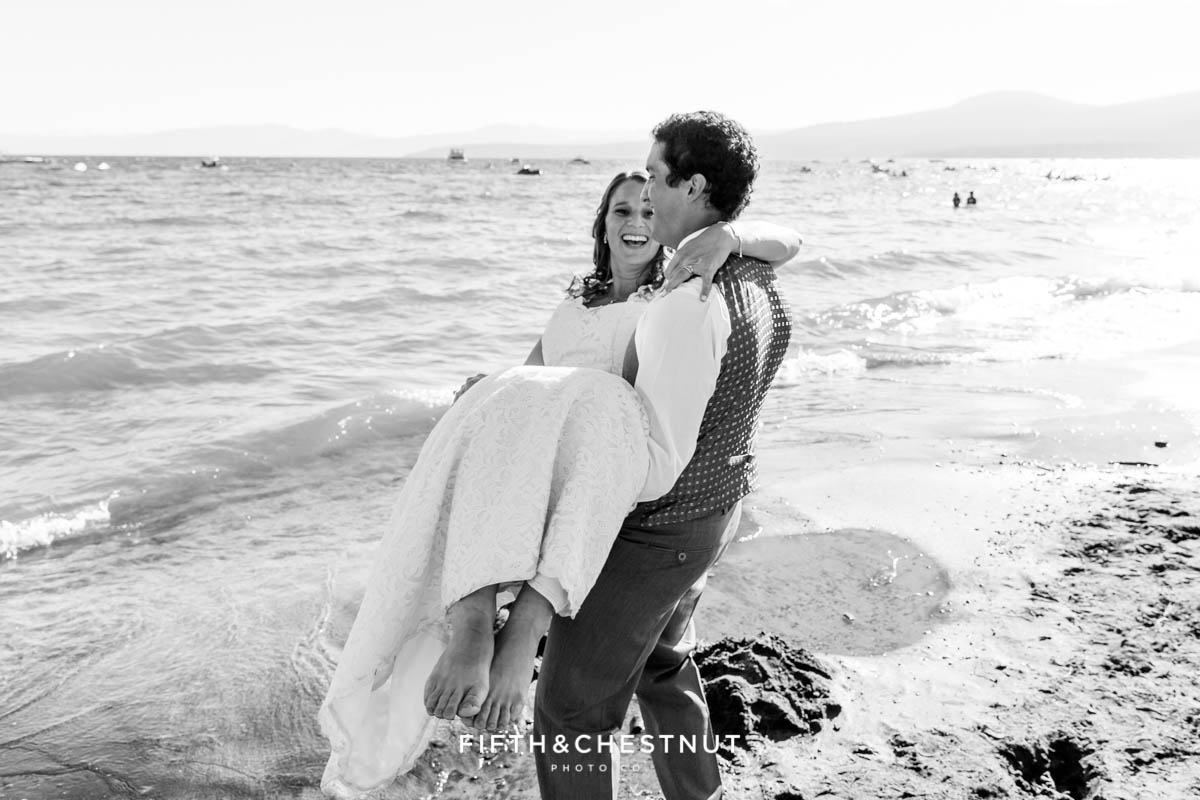 Groom carries bride to the beach for their Tahoe wedding