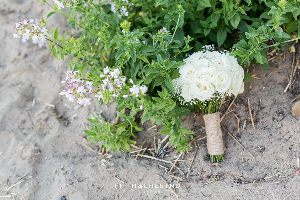Wedding bouquet of roses propped up against a flowery bush on the beach of North Lake Tahoe