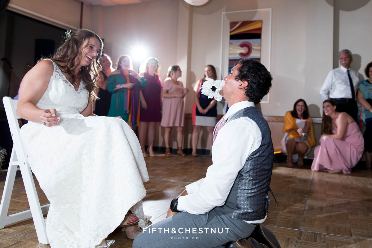 Groom gets the garter from under the bride's custom gown made in Ecuador for their North Lake Tahoe Wedding by Lake Tahoe Wedding Photographer