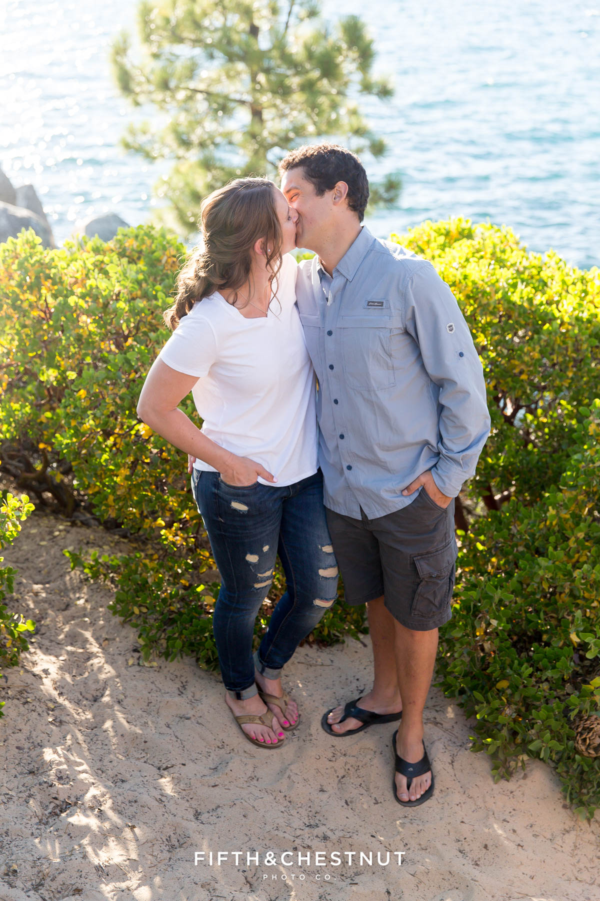 couple kissing in front of manzanita backlit by the setting sun at Sand Harbor for a summer Tahoe engagement by Lake Tahoe Wedding Photographer