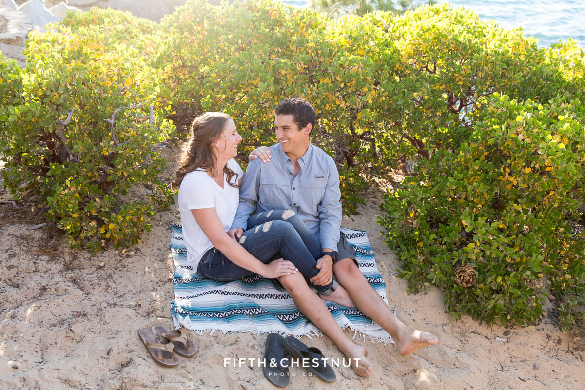 couple sitting on blanket on the sand of Lake Tahoe beach surrounded by manzanita as the sun glows behind them for their summer Tahoe engagement