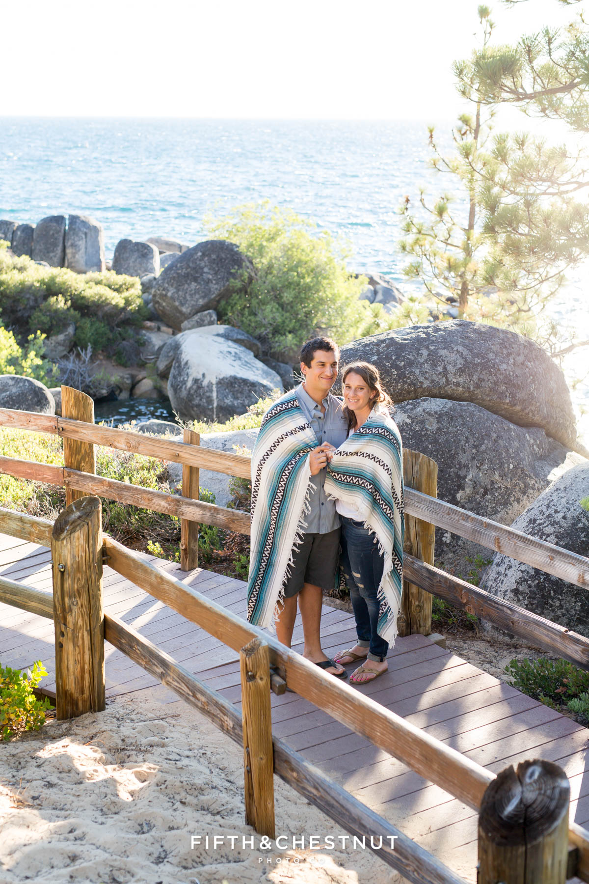 couple huddles in south american style blanket for their summer Tahoe engagement on the nature path at Sand Harbor